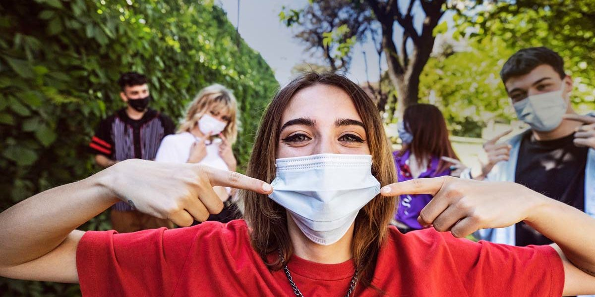 Group of teenagers posing showing their protective face masks during Covid-19 Coronavirus epidemic spread.